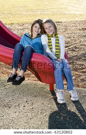 Close-up of young friends (10-11 years) posing together outdoors on playground slide