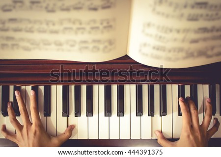 Close up of young girl hands, playing piano. vintage tone filter effected - stock photo
