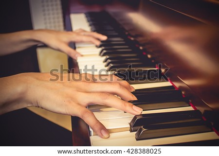Close up of young girls hands, playing piano. vintage tone filter effected - stock photo
