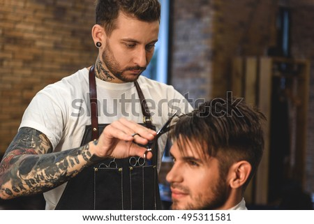 close up of young hairstylist working in barbershop
