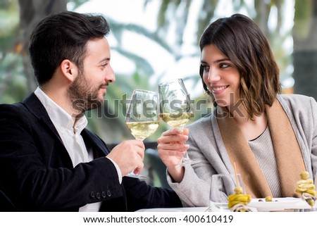 Close up of young handsome Couple sharing special moment white wine in restaurant. - stock photo