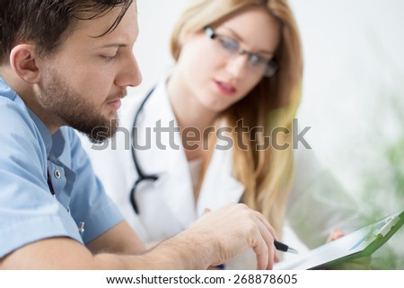 Close-up of young handsome doctor looking at medical history - stock photo