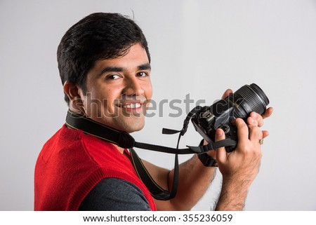 Close-up of young handsome indian photographer taking a photograph, asian man holding camera, indian man with camera, young professional indian photographer, young asian photographer - stock photo