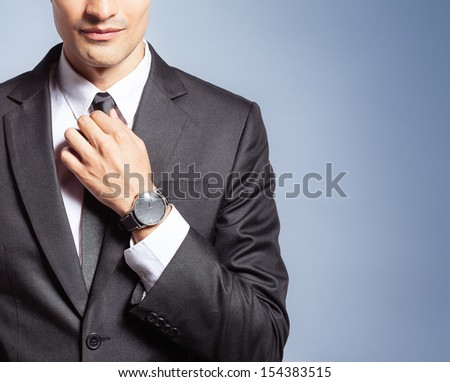 Close up of young handsome man in black suit isolated on blue background - stock photo
