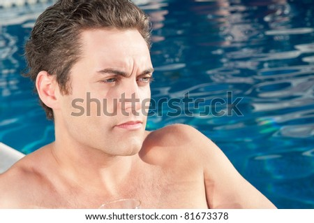 Close-up of young handsome man lost in thoughts near swimming pool - stock photo