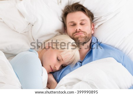 Close-up Of Young Happy Couple Sleeping Together In Bed At Home
