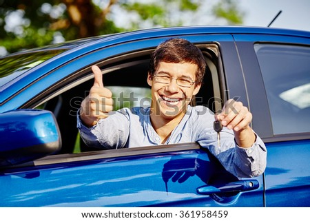 Close up of young happy hispanic man wearing glasses holding out car keys, showing thumb up hand gesture and smiling through car window - new drivers concept - stock photo