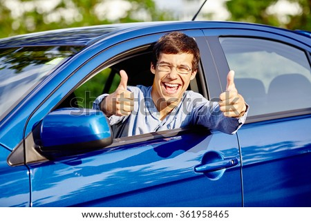 Close up of young happy hispanic man wearing glasses showing thumb up hand gesture with both hands and laughing through car window - new drivers concept - stock photo