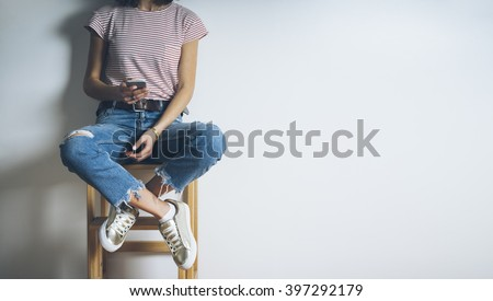 Close-up of young hipster girl wearing blue ripped jeans and using modern smartphone on a blank white background with copy space for your content, stylish woman sitting on a chair and using cellphone  - stock photo