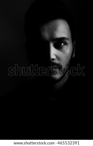 Close up of young hipster posing in art studio, black & white
