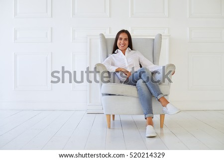 Close-up of young joyous woman in casual outfit sitting against white brick background in the middle of the room