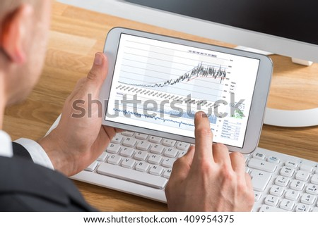 Close-up Of Young Male Stock Market Broker Working On Digital Tablet At Computer Desk - stock photo