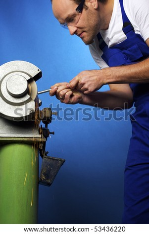Close-up of young male technician in blue overall working on grinding bench in workshop, isolated on blue background. - stock photo