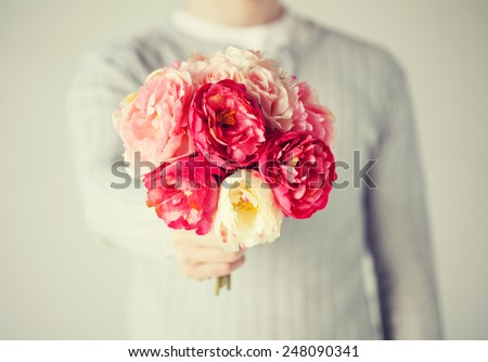 close up of young man giving bouquet of flowers. - stock photo