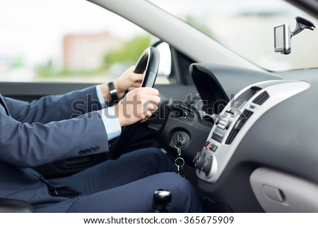 close up of young man in suit driving car - stock photo