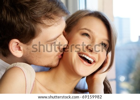 Close-up of young man kissing happy woman - stock photo
