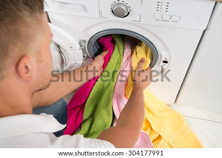 Close-up Of Young Man Loading Colorful Towels Into The Washing Machine