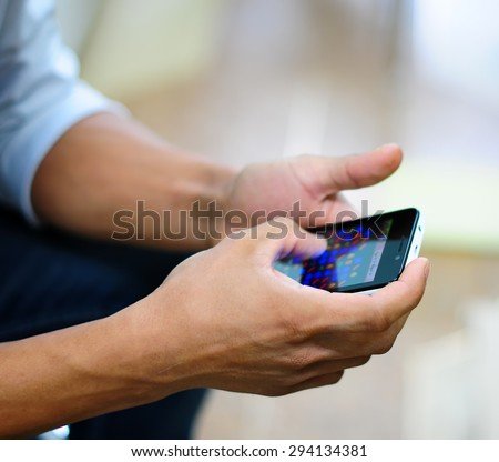 Close-up Of Young Man Playing Video Game On Mobile - stock photo