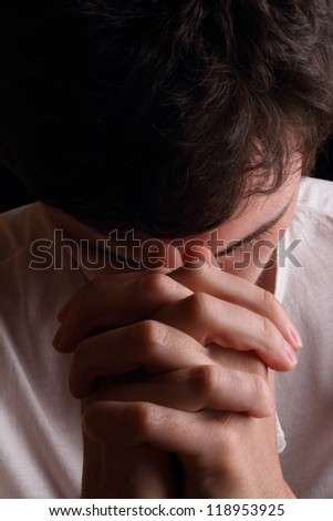 Close-up of young man praying - stock photo