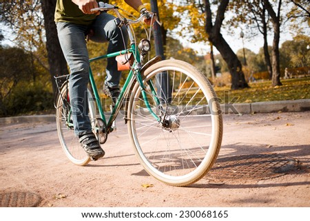 Close-up of young man riding bicycle in park - stock photo