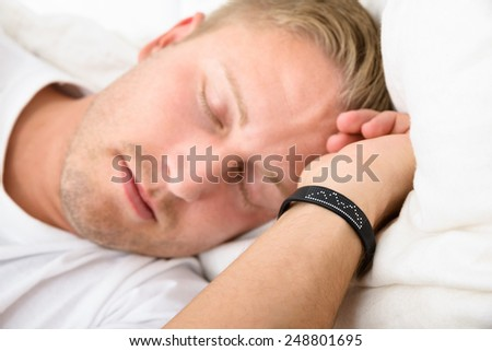 Close-up Of Young Man Sleeping Wearing Smart Wristband - stock photo