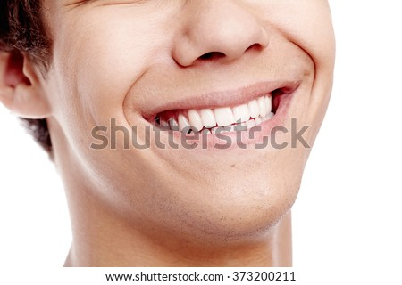 Close up of young man smiling with perfect healthy white teeth isolated on white background - dental care concept - stock photo