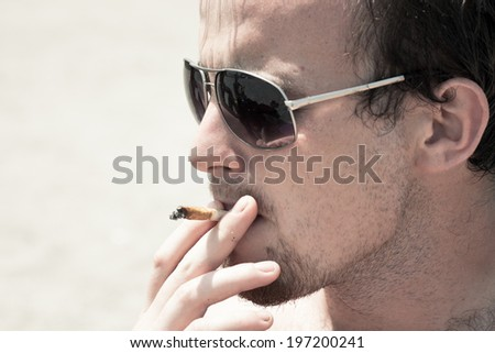 Close up of young man smoking hashish joint. - stock photo