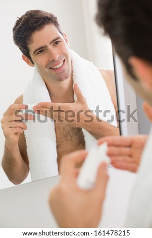 Close up of young man with reflection putting moisturizer on his face - stock photo