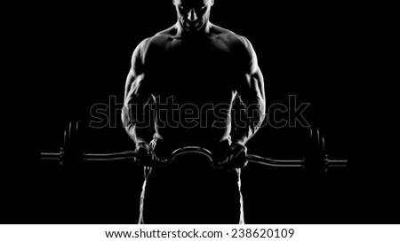 Close up of young muscular man lifting weights over dark backgro - stock photo