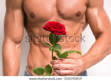 Close-up of young muscular man with perfect torso holding single rose while standing against white background.