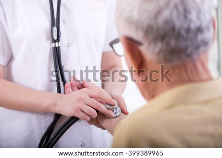 Close up of young nurse listening heartbeat with stethoscope on the old man's hand - stock photo