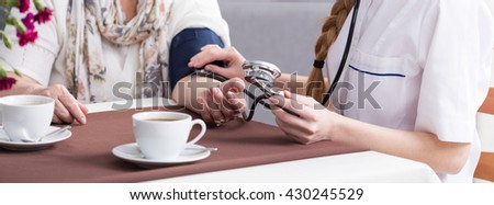 Close-up of young nurse measuring her patient blood pressure during coffee break at nursing home - stock photo