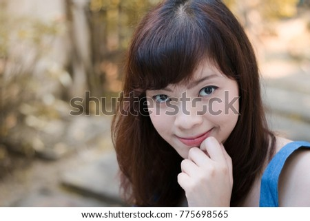 Close up of young pretty Asian woman in the garden.