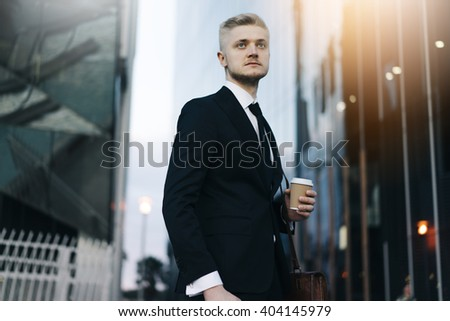 Close-up of young professional employer in modern suit standing near skyscrapers at early morning with coffee, flare light - stock photo