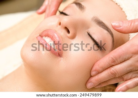 Close-up of young relaxing beautiful woman having facial massage with massage oil - stock photo