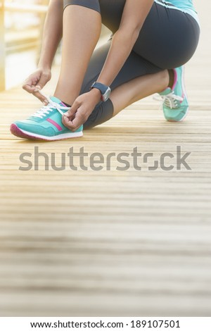 Close up of young runner tying shoe lace on wooden boardwalk at sunrise - stock photo