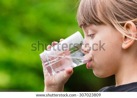 Close-up of young scandinavian child drinking fresh and pure tap water from glass with a blurred green background. - stock photo
