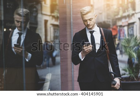 Close-up of young serious businessman wearing black suit and using smartphone outdoors, successful male professional ceo walking on the street at sunny city, flare light - stock photo