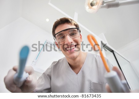Close-up of young smiling dentist holding dental tools - stock photo