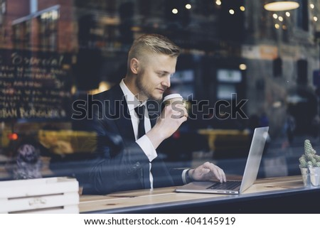 Close-up of young successful businessman wearing black suit and using modern laptop in coffee shop while reading in internet information - stock photo