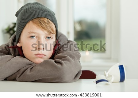 Close Up of Young Teenage Boy Wearing Hoodie and Winter Cap Looking Remorseful While Leaning on Arms in Kitchen with Broken Mug on Table - stock photo