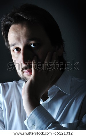 Close-up of young thinking man resting chin on palm, low key - stock photo