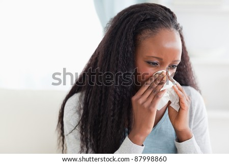 Close up of young woman blowing her nose - stock photo