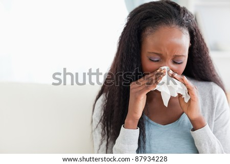 Close up of young woman blowing her nose on couch - stock photo