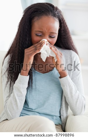 Close up of young woman blowing her nose on sofa - stock photo