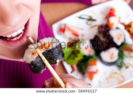 close-up of young  woman eating sushi  front view - stock photo