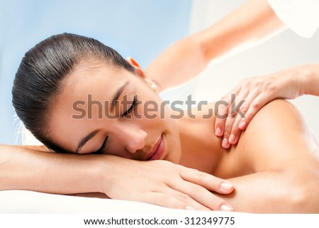 Close up of Young woman enjoying spa treatment. Therapist doing manipulative massage on shoulders. - stock photo