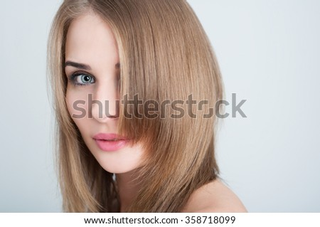 Close-up of young woman face with perfect smooth skin on studio background