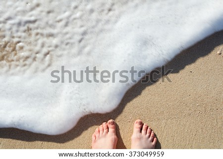 Close up of young woman feet on a tropical sandy beach - stock photo