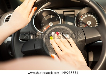 Close-up Of Young Woman Hand On Horn Button - stock photo